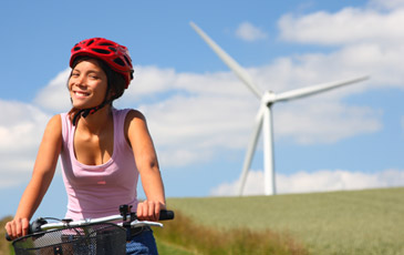 Girl cycle by wind turbine